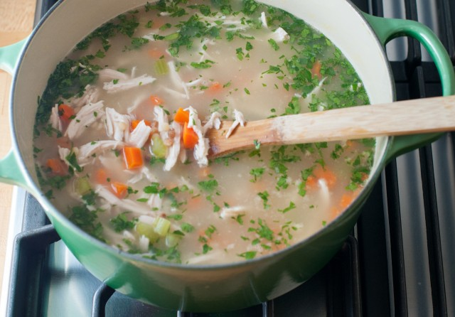 adding the chicken and the parsley to the soup