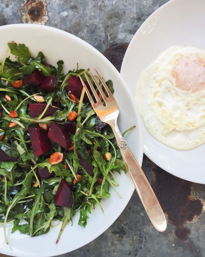 roasted beet and arugula salad with toasted almonds and fried egg